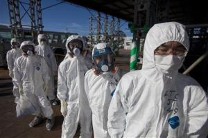 Workers in protective suits and masks wait to enter the emergency operation center at the crippled Fukushima Dai-ichi nuclear power station in Okuma, Japan.