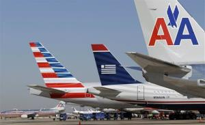 In this Thursday, Feb. 14, 2013 file photo, US Airways and American Airlines planes are shown at gates at DFW International Airport in Grapevine, Texas.