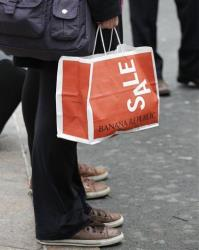 A shopper carries a Banana Republic bag in this file photo.