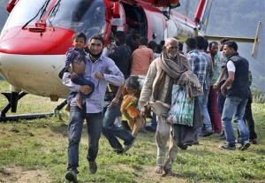 In this Friday June 21, 2013 photo, Indian pilgrims who were stuck in the upper reaches of mountains are brought to safer place, in Joshimath, in northern Indian state of Uttrakhand. Officials say soldiers are working to evacuate tens of thousands of people still stranded in northern India where nearly...