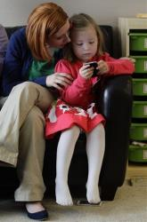 Coy Mathis plays with a smart phone as her mother, Kathryn, watches, at their home in Fountain, Colo., Monday Feb. 25, 2013.