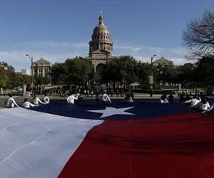 A large Texas flag is carried up Congress Avenue towards the Texas Capitol.