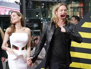 Angelina Jolie, left, and Brad Pitt arrive for the film premiere World War Z  in Berlin, Germany, Tuesday, June 4, 2013 .