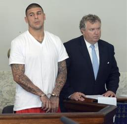 Aaron Hernandez stands with attorney Michael Fee during arraignment in Attleboro District Court Wednesday.