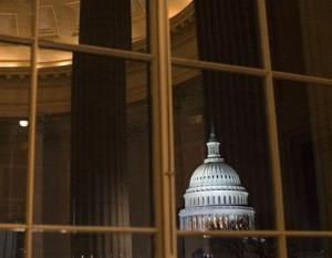 In this photo taken Jan. 2, 2013, a reflection of the US Capitol is seen inside the Cannon House Office Building.