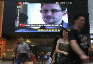 A TV screen shows a news report of Edward Snowden.