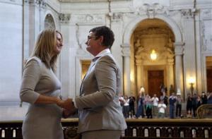Sandy Stier, left, exchanges wedding vows with Kris Perry during a ceremony presided by California Attorney General Kamala Harris at City Hall in San Francisco Friday.