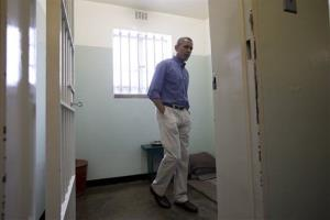 President Obama looks out from Section B, prison cell No. 5, on Robben Island, South Africa, Sunday, June 30, 2013. This was Nelson Mandela's cell for 18 years of his 27-year prison term.