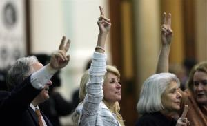 In this June 25, 2013, file photo, Sen. Wendy Davis, center, holds up two fingers to signal a No vote as the session where she tried to filibuster an abortion bill draws to a close in Austin, Texas.