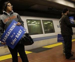 In this Tuesday, June 25, 2013 file photo, Jeanette Sanchez holds a sign supporting Bay Area Rapid Transit workers as she waits for a train at the 24th Street Mission station in San Francisco.