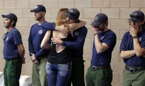 A woman hugs a firefighter as they wait to go inside for a memorial service in Prescott, Arizona yesterday.