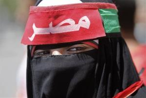 A veiled Egyptian woman wears a head band in Arabic that reads,Egypt, during a protest in Tahrir Square.