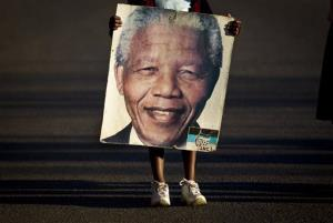 Lehlogonolo Nkosi, 7, holds a portrait of Nelson Mandela as she leaves the Mediclinic Heart Hospital where Nelson Mandela is being treated in Pretoria, South Africa, July 3, 2013.