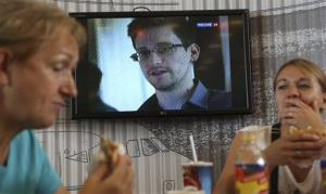 In this Wednesday, June 26, 2013 file photo, transit passengers eat at a cafe with a TV screen showing a report on Edward Snowden, at Sheremetyevo airport in Moscow, Russia.