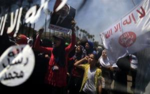 Supporters of ousted Egyptian President Mohammed Morsi are seen through an Islamist flag as they chant slogans during a rally near the University of Cairo, Giza, Egypt, Friday, July 5, 2013.