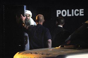 Radical Muslim preacher Abu Qatada, left, prepares to board a private flight bound for Jordan, in London, Sunday, July 7, 2013.