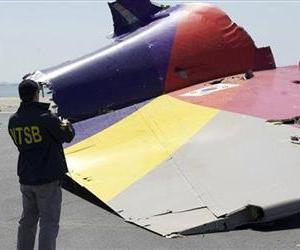 This image released by the National Transportation Safety Board, Sunday, July 7, 2013, shows an NTSB agent photographing a part of the Boeing 777 Asiana Airlines Flight 214 aircraft.