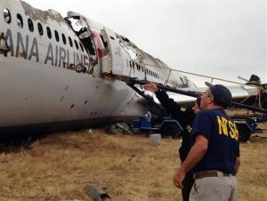 Authorities investigate the crash. NTSB chief Deborah Hersman is pointing toward the plane.