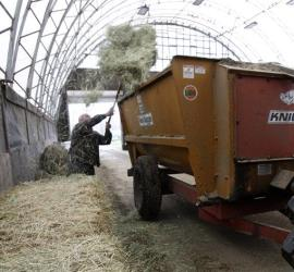 This file photo shows farmer Myles Goodrich loading a feed wagon at his farm in Danville, Vt.