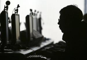 A computer user is silhouetted with a row of computer monitors at an Internet cafe.