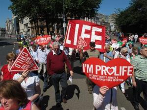 Anti-abortion protesters holding placards walk through Ireland's capital, Dublin, in an anti-abortion protest Saturday, July 6, 2013.