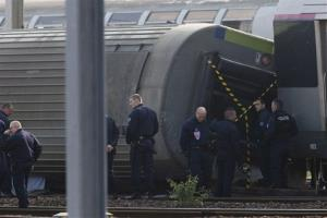 Police officers investigate on the site where a train derailed at a station in Bretigny sur Orge, south of Paris, Saturday, July 13, 2013.