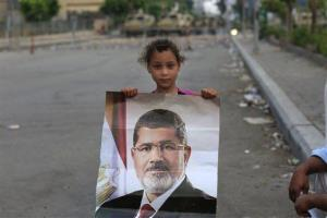 A young supporter of ousted Egypt's President Mohammed Morsi poses with his photo.