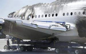 A man walks behind the wreckage of Asiana Flight 214 on Friday.