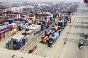 Containers are piled at a port in Qingdao in eastern China's Shandong province. China says imports and exports both fell abruptly in June.