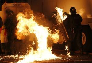 A Molotov cocktail hits riot police after being thrown by loyalist rioters in north Belfast, Northern Ireland.