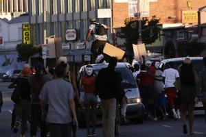 A protester stomps on a van during a demonstration in Los Angeles yesterday.