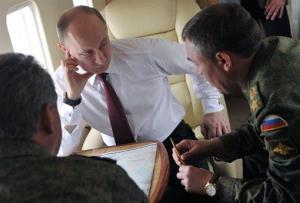 Russian President Vladimir Putin, center, and Defense Minister Sergei Shoigu, left, listen to Russia's military's General Staff Valery Gerasimov during military exercises.