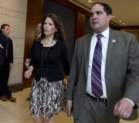 This June 11, 2013 file photo shows Rep. Michele Bachmann, R-Minn., arriving with staff member Javier Sanchez on Capitol Hill in Washington.