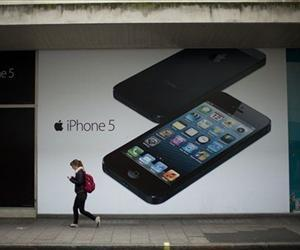 A woman walks past an ad for the Apple iPhone 5 in London, Wednesday, Dec. 19, 2012.