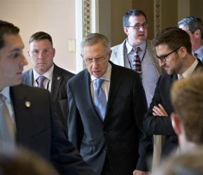 Senate Majority Leader Harry Reid center, walks to closed-door meeting yesterday.