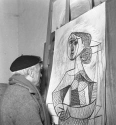 In this 1953 file photo, artist Pablo Picasso looks at a Portrait of a Woman in his studio in Vallauris, French Riviera.