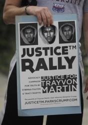 A demonstrator holds up a sign as he attends a vigil for Trayvon Martin in Miami.
