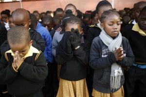 Students at the Denver Primary School in Johannesburg, South Africa, pray for ailing former South African President Nelson Mandela on the occasion of his 95th birthday.
