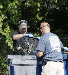 Investigators take a black trash bag from a dumpster Sunday, July 21, 2013 near where three bodies were recently found in East Cleveland, Ohio.