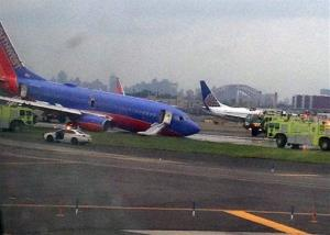 A Southwest Airlines plane whose nose gear collapsed as it touched down on the runway is surrounded by emergency vehicles at LaGuardia Airport.
