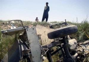 Afghan men investigate the site of roadside bomb attack in Helmand southern of Kabul, Afghanistan, Thursday, June, 11, 2013.