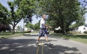 Ohio letter carrier Keith McVey walks his route delivering mail in a neighborhood in Akron, Ohio on Friday, July 16, 2010.