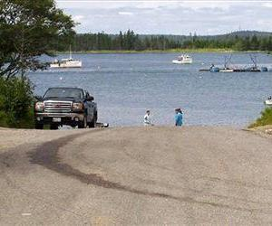 Two men walk on the boat ramp at the scene of a double fatal accident, Wednesday July 24, 2013, in Roque Bluffs, Maine.