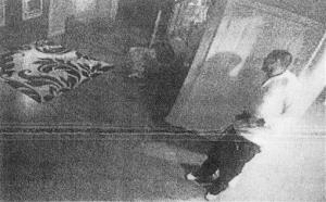 This black and white photo taken from former New England Patriot Aaron Hernandez's home surveillance system in North Attleborough, Mass., and released in documents by the Attleboro District Court Thursday, July 25, 2013, shows Hernandez holding what authorities said appears to be a gun, shortly after Odin Lloyd was shot...