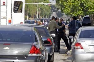 Hialeah police officers talk outside the apartment building where the shootings took place.