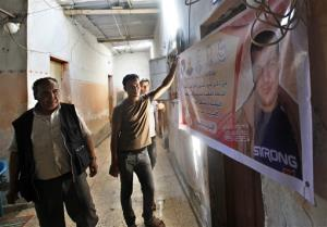 In this Friday, July 26, 2013, photo, Issa Masoud, 75, left, helps his sons put up a banner of his jailed son at Shati Refugee Camp in Gaza City.