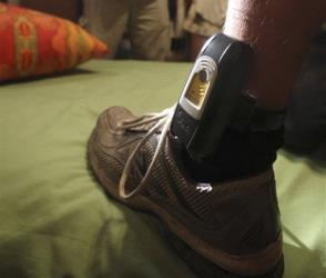 A parole agent uses a flashlight to inspect a GPS locater worn on the ankle of a parolee in Rio Linda, Calif.