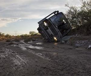 A tour bus lays on its side up against a bank of a wash, Sunday, July 28, 2013, near Dolan Springs, Ariz.