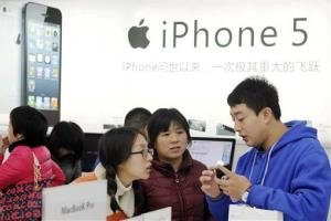 A storekeeper introduces iPhones to customers near an iPhone 5 advertisement at an Apple products shop in Dongyang, in eastern China's Zhejiang province, Friday, Dec. 14, 2012.
