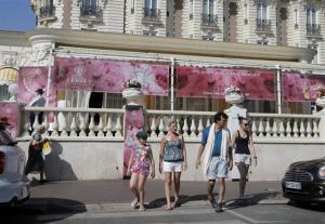 People walk by the Carlton hotel, in Cannes, southern France, the scene of a daylight raid, Sunday, July 28, 2013.